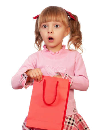 cute little girls: Surprised christmas girl holding shopping bag. Isolated on white background. Stock Photo