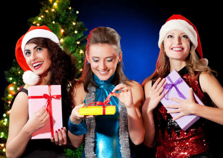 Christmas women with gifts near a Christmas tree photo