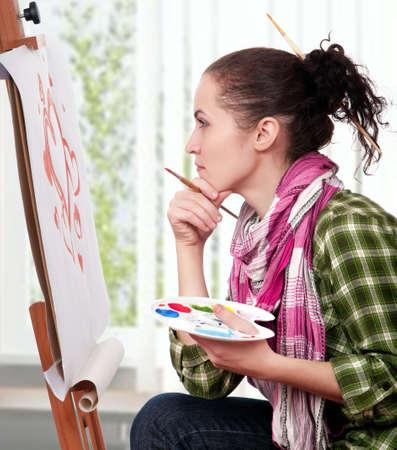 creativity artist: Bella joven con pinceles cerca de caballete, pintura sobre lienzo. Foto de archivo