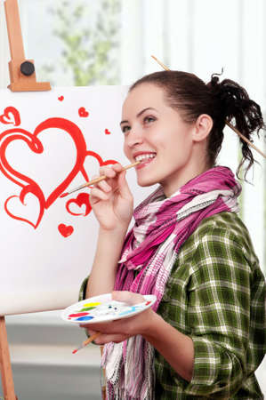 Beautiful girl with brushes near easel, painting on canvas. photo
