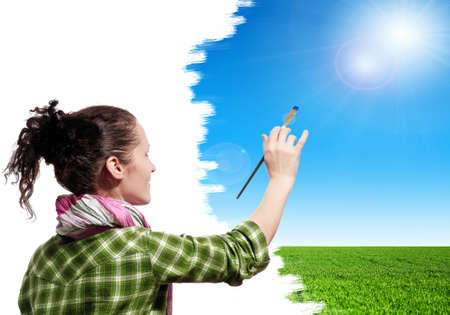 Beautiful girl with paint brush paints the sky photo