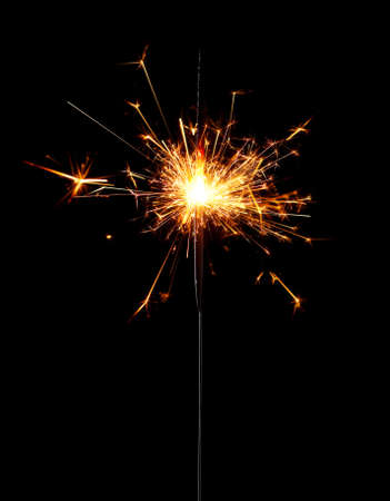 Burning christmas sparkler isolated on black background photo
