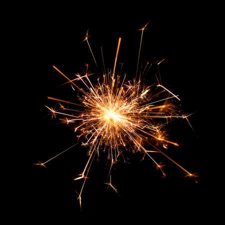Burning christmas sparkler isolated on black background photo