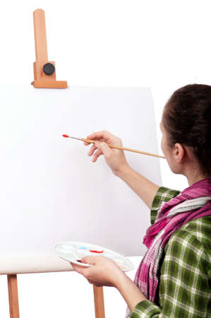 Beautiful girl with brushes near easel, painting on canvas