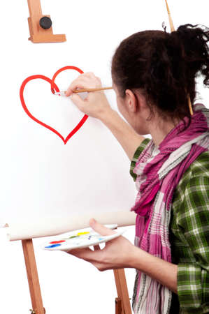 work heart: Girl with paint brush near easel, painting red heart on canvas. Stock Photo