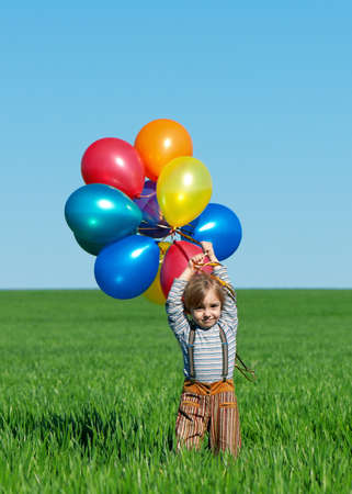 Happy girl with balloons walking on the spring field photo