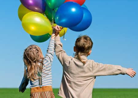 Happy sister and brother with balloons walking on the spring field photo