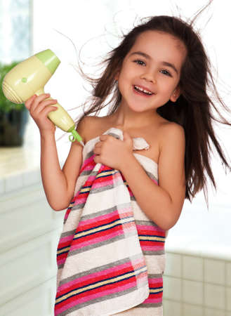 Little girl dries hair after bathing in bathroom photo
