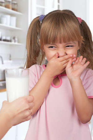 insipid: Cute little girl and glass of milk in kitchen Stock Photo