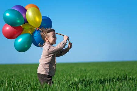 niño corriendo: Niño feliz con globos que se ejecutan en el campo de la primavera.