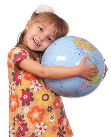 Smiling little girl holding globe. Isolated on white background. photo