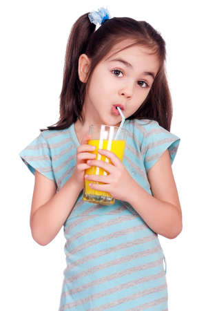 gripping hair: Portrait of happy little girl drinking orange juice Stock Photo