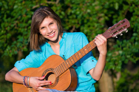 Beautiful teenage girl with guitar in the green park photo