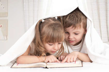 child book: Lovely children - brother and sister, reading a book, on the bed Stock Photo