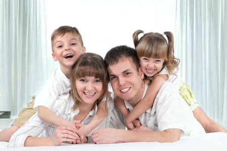Young happy family playing together on a bed Stock Photo - 9037927