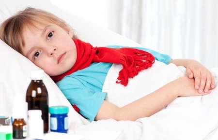 ni�os enfermos: Enferma hermosa ni�a con un pa�uelo rojo en la cama Foto de archivo