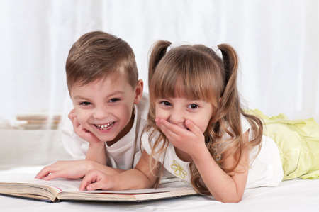 Lovely children - brother and sister, reading a book, on the bed photo