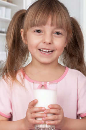 Cute little girl and glass of milk in kitchen photo