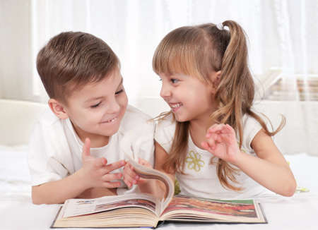 storytelling: Lovely children - brother and sister, reading a book, on the bed Stock Photo
