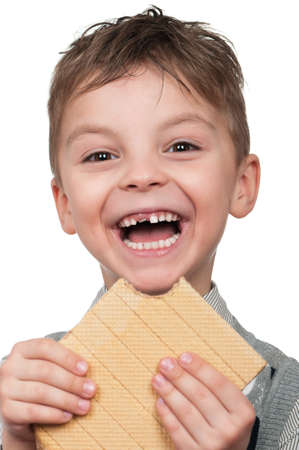 hungry children: Portrait of a cute boy having a waffle - isolated on white