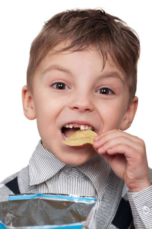 hungry children: Portrait of a cute boy eating potato chips - isolated on white Stock Photo
