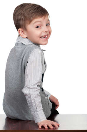 Portrait of happy boy sitting on desk - isolated on white photo
