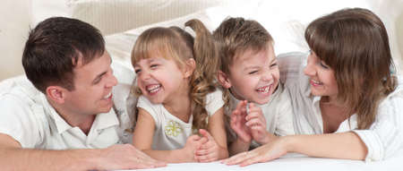 Young happy family playing together on a bed photo