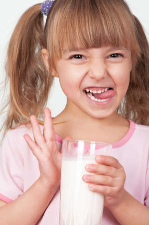 Cute little girl with glass of milk on light background photo