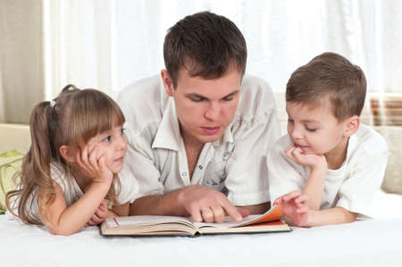 Lovely family - father with children, reading a book, on the bed photo