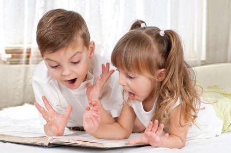 suddenness: Lovely children - brother and sister, reading a book, on the bed Stock Photo