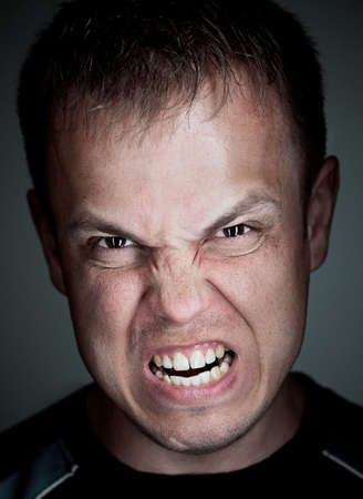 Angry caucasian man. Close-up portrait on grey background.