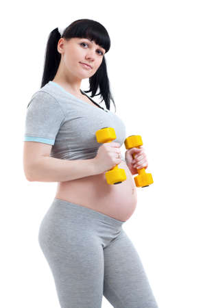 Pregnant woman in a fitness workout using hand weights on white background. photo