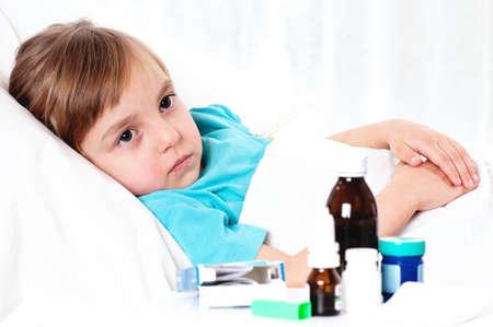 enfant malade: Malade peu belle fille avec un foulard rouge dans le lit