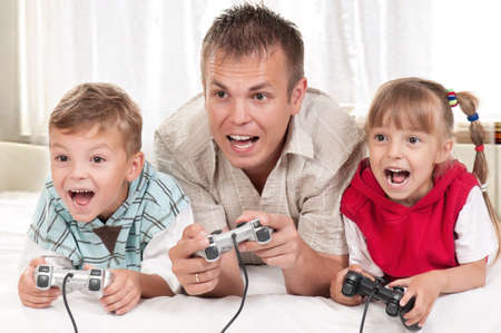 Happy family - father and children playing a video game photo