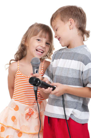 buddies: Funny little boy and girl singing with a microphone isolated on white background
