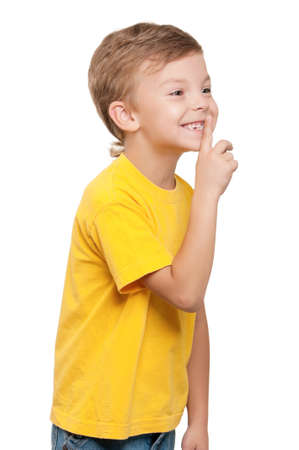 Portrait of beautiful little boy with silence gesture over white background photo
