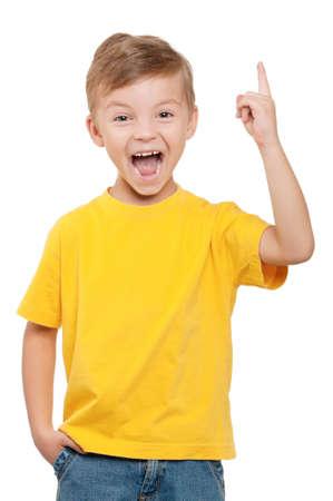 Enthousiaste petit garçon pointant vers le haut sur fond blanc