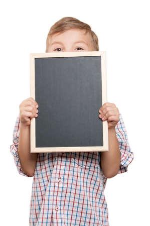 Portrait of a little boy holding a blackboard over white background