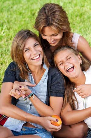 adolescentes riendo: Madre feliz con sus hijas en el parque al aire libre