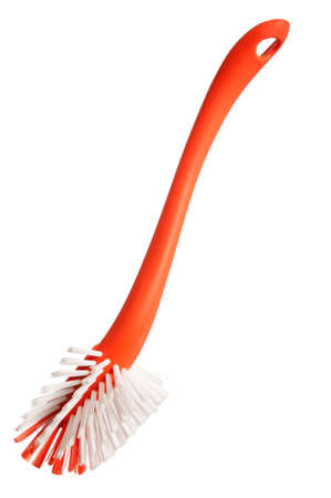 Plastic orange brush for washing dishes on a white background photo