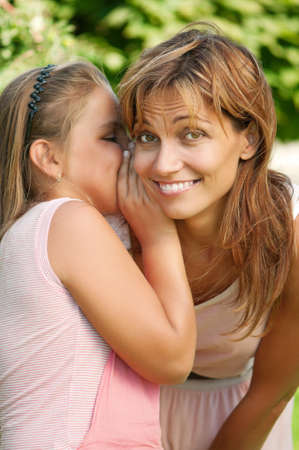whisper: Happy mother with her daughter in park outdoors Stock Photo