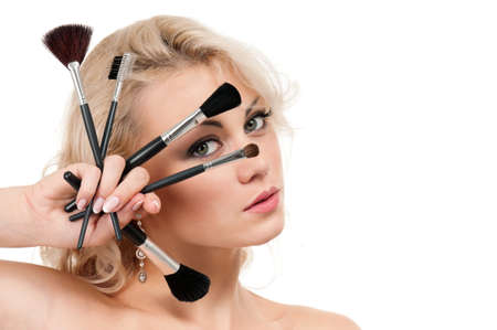 Portrait of young beautiful woman with makeup brushes over white background Stock Photo - 10776425