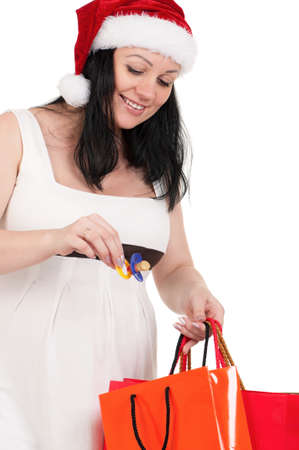 Portrait of a pregnant woman in santa hat holding a shopping bags over white background photo