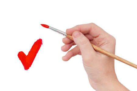 Female hand holding paint brush isolated over white background photo