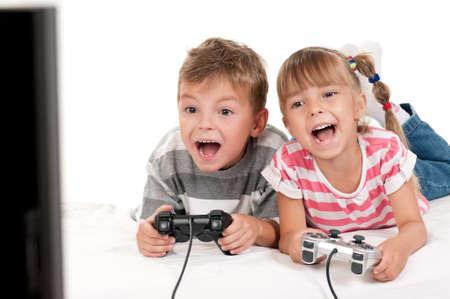 niños jugando videojuegos: Felices a los niños - los niños y niñas jugando con un videojuego
