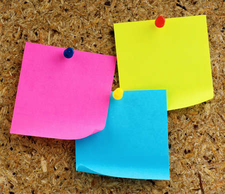 Papel de notas con push pins en cartelera Foto de archivo