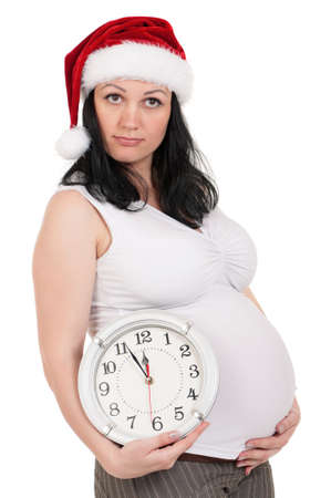 Portrait of a pregnant woman in santa hat with clock over white background. Third trimester. photo