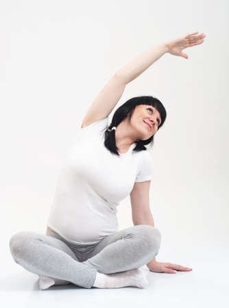 Pregnant woman in a fitness workout on grey background Stock Photo - 10843191