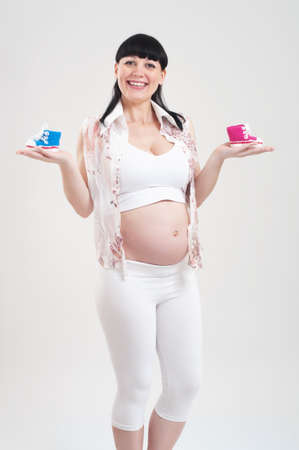 Pregnant woman holding a babys bootees in different colours photo