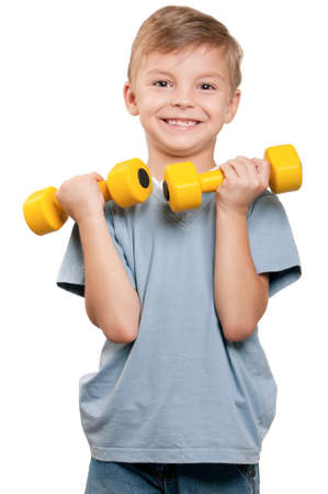 Portrait of a healthy little boy working out with dumbbells over white background photo